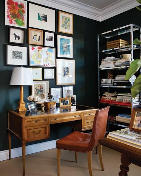 Foto de uma cadeira posicionada em frente a uma mesa de madeira. Ao lado dela há uma estante de ferro alta que guarda diversos itens de escritório.