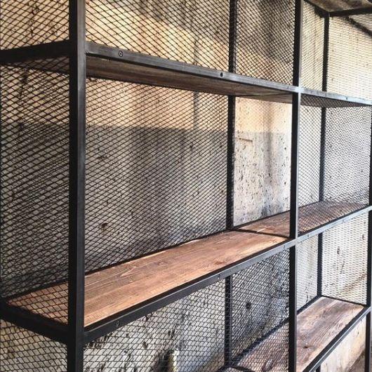 Foto em close up de uma estante com as extremidades feitas em aço e a parte interna feita com madeira.