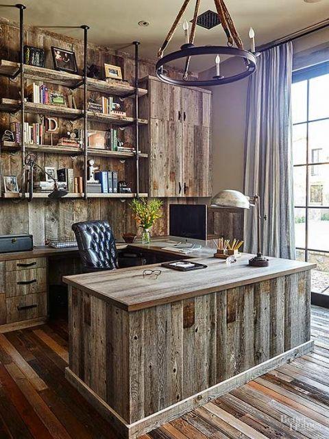 Ambiente completamente decorado com madeira rústica. Há uma mesa com objetos de escritório e um computador. Atras da mesa há quatro estantes de madeira paralelas sustentadas por vigas de ferro ligadas ao ferro.