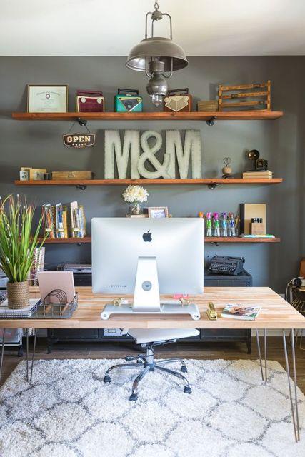 Foto de um escritório onde há uma mesa de madeira com um computador. Atrás da mesa há três estantes de madeira uma acima da outra. Elas estão instaladas diretamente na parede e servem de suporte para diversos objetos de decoração.