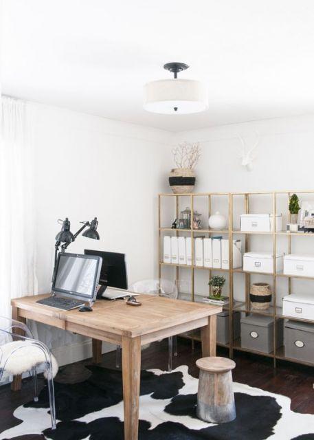 Foto de uma mesa de madeira com dois computadores contrapostos. Atrás da mesa há uma estante de madeira que guarda diversas pastas e caixas.