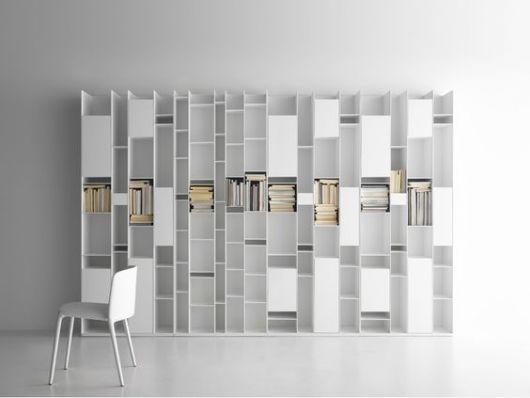 Ambiente vazio completamente branco com uma prateleira em design futurista de MDF e livros posicionados em algumas de suas aberturas.