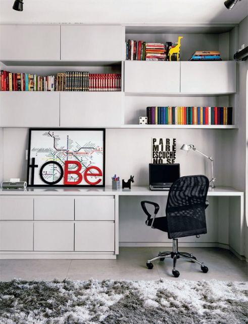 Ambiente de Home Office com mesa e estantes em MDF onde são colocados livros, objetos de decoração e um notebook em frente a uma cadeira.