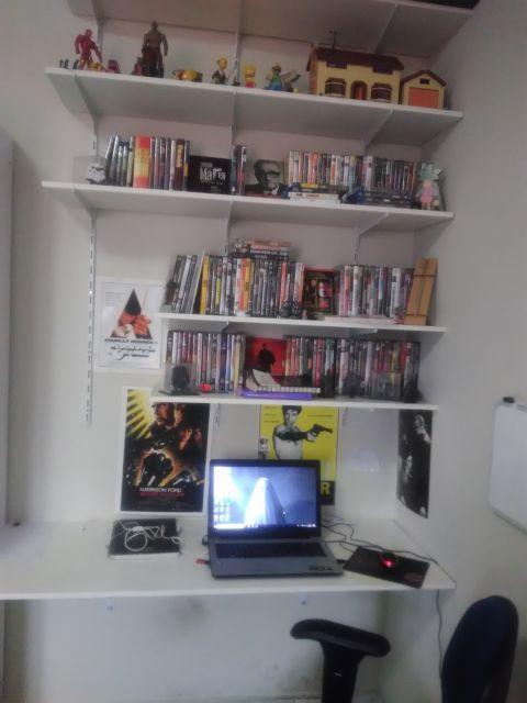 Mesa de MDF com um notebook e acima dela diversos prateleiras com DVDs e objetos de decoração.