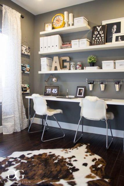 Ambiente decorado com diversas estantes em MDF paralelas na parede e a mais baixa serve como uma mesa de escritório.