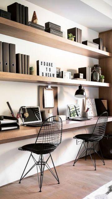 Três estantes paralelas na parede com livros, notebook e objetos de decoração nelas. Há duas cadeiras em frente à estante mais baixa.