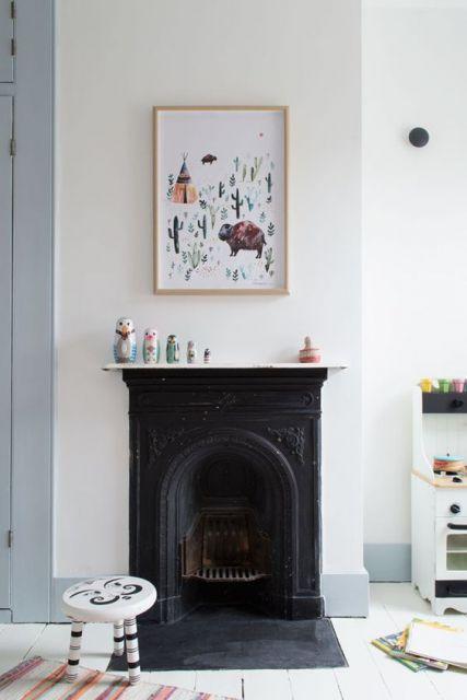 Foto de uma parede com um quadro e abaixo dele uma lareira de ferro bem antiga.