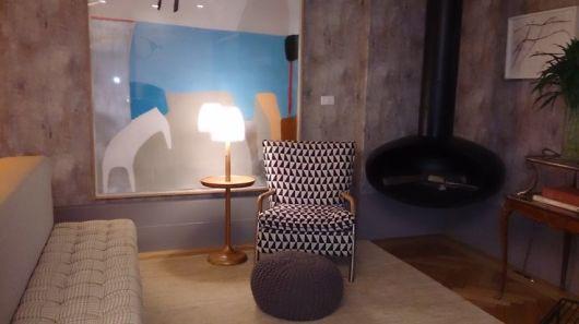 Foto de um ambiente com uma poltrona em frente a um quadro cubista. Ao lado da poltrona há uma lareira de canto de ferro suspensa.