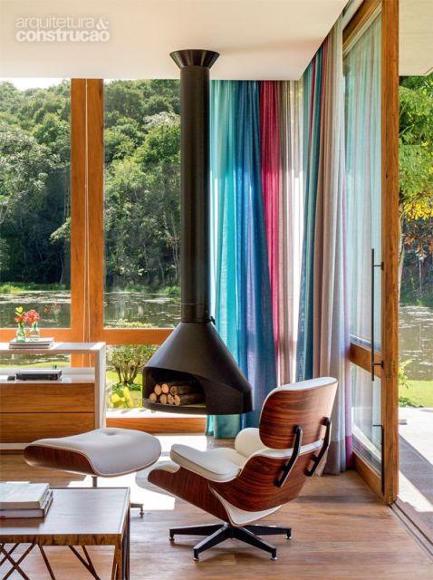 Foto de um ambiente feito com paredes grandes de vidro. No canto há uma lareira suspensa com lenhas em seu interior.