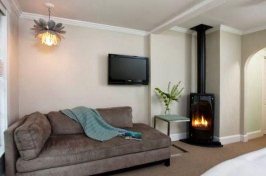 Foto de uma sala com uma lareira de canto ao lado do sofá. Sua base vai até mais ou menos metade da altura da parede e um cano liga ela ao teto.