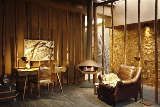 Foto de um ambiente com decoração rústica e uma lareira de canto suspensa acesa.