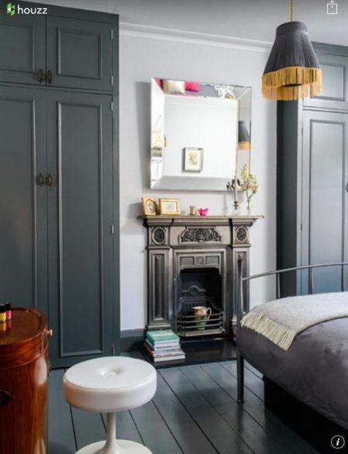 Foto de um quarto mostrando parte da cama e do armário. Na parede há um espelho e abaixo dele uma lareira de ferro embutida com decoração antiga.
