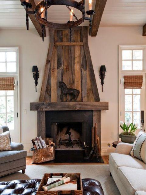 Foto de uma lareira de ferro no centro do ambiente decorada com grandes peças de madeira que cobrem toda a extensão vertical da parede.