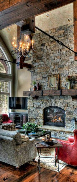 Foto de ambiente com decoração rústica onde há uma grande parede saliente com tijolos expostos. Nela há uma lareira de ferro em formato oval acesa.
