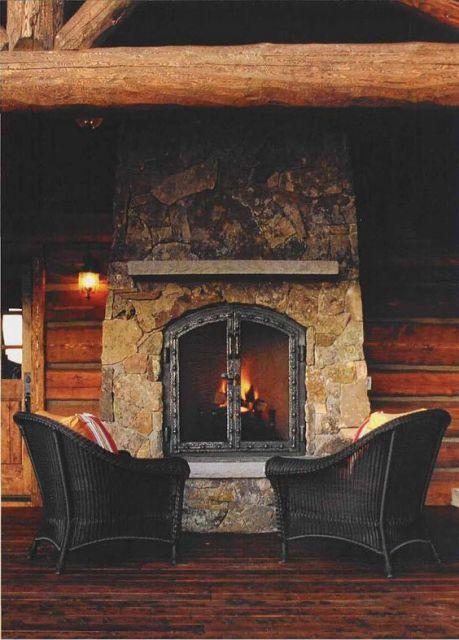 Foto de duas poltronas posicionadas em frente a uma parede rústica onde uma lareira de ferro está acesa.