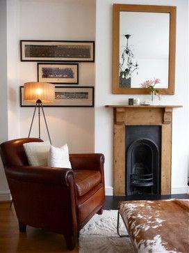 Foto de uma sala decorada com poltrona, tapete, quadros e espelho. Abaixo do espelho há uma lareira de ferro embutida na parede decorada com madeira em seu entorno.