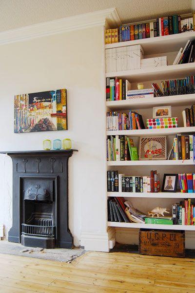 Foto de um ambiente com uma parede repleta de estantes com livros. Ao lado da estante há uma lareira de ferro embutida na parede.