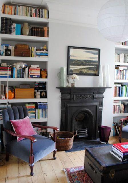Foto de um ambiente com uma poltrona e duas prateleiras repletas de livros. Entre elas há uma lareira de ferro embutida na parede.