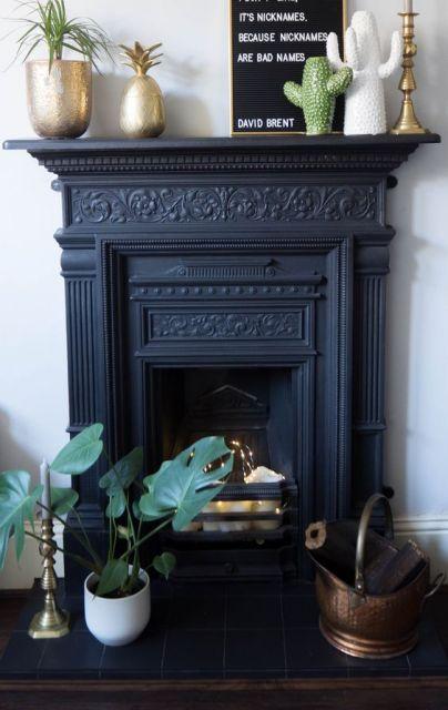 Foto de uma lareira decorada com ferro. Ela também serve de apoio para elementos decorativos como um quadro e duas plantas.