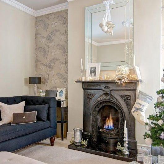 Foto de uma sala de estar com uma lareira de ferro embutida na parede no centro. A lareira está acesa e tem elementos decorativos posicionados sobre ela.