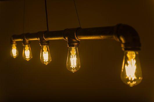 Foto de um cano pendurado no teto com saída para cinco lâmpadas colocadas lado a lado.