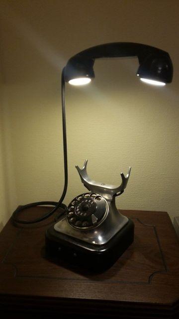 Foto de uma lâmpada em formato de telefone. A iluminação sai de dois pontos diferentes, um onde colocamos a boca e outros onde colocamos o ouvido.