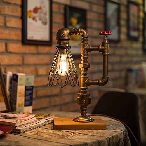"""Foto de uma luminária retrô em cima de uma mesa. Seu """"corpo' é feito com canos e a extrema tem uma lâmpada."""