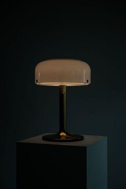 Foto de uma luminária que se parece com um abajur. Ela está em uma mesa em um ambiente escuro e não está acesa;.