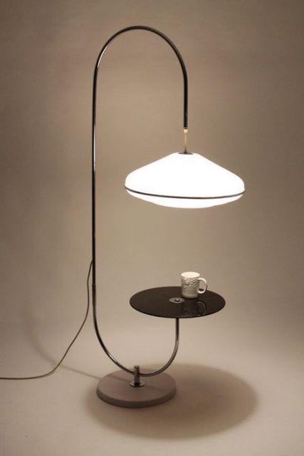 Foto de uma luminária que tem apenas uma linha sinuosa como base de sustentação. Em uma das pontas está uma plataforma reta que pode servir de apoio a objetos e na outra está uma lâmpada forte.