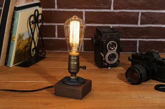 Foto de uma luminária simples ligada à tomada e posicionada a uma mesa. Ela tem uma base de madeira e tem um botão que regula sua intensidade.