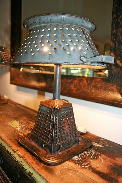 Foto de uma luminária que se parece com um abajur feita de objetos comuns. A base é feita a partir de um ralador de queijo e o topo de um escorredor de macarrão, cujos furos permitem a saída da luz.