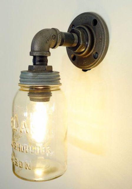 Foto de uma luminária pendurada na parede. A sustentação é feita a partir de um material metálico e a lâmpada é coberta por um vidro.