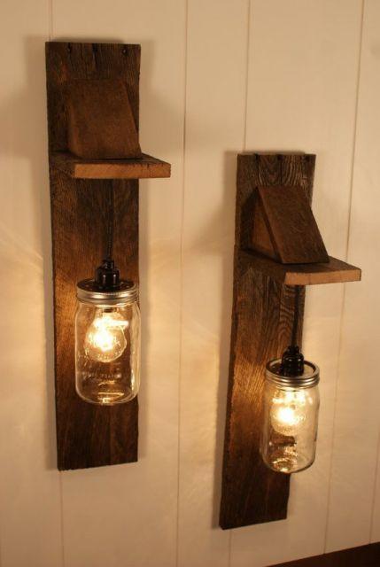 Foto de duas luminárias de parede. As duas são fixadas a uma base de madeira instalada na parede por meio de uma corrente e tem um pote de vidro para cobrir a lâmpada.