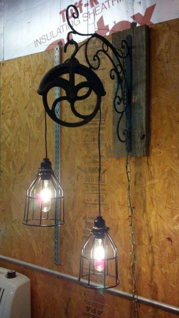 Duas lâmpadas penduradas em uma roldana fixada na parede. As lâmpadas são cobertas por um objeto metálico com certas aberturas em sua dimensão.