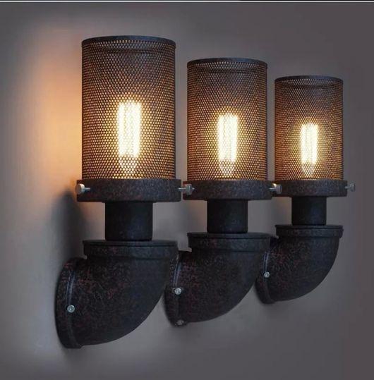 Foto de três luminárias iguais lado a lado. Elas estão voltadas para cima e seu base se assemelha a um cano. A lâmpada é coberta por uma estrutura de metal resistente que tem diversos furinhos.