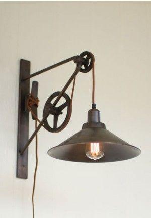Foto de uma luminária suspensa por meio de corda que a liga em uma roldana pendurada na parede.