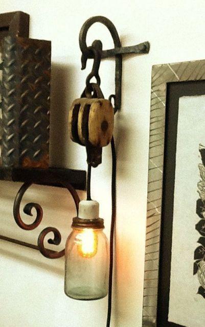 Foto de uma lâmpada coberta por um recipiente de vidro. Ela é ligada por meio de um fio a uma estrutura pendurada por um gancho em um objeto metálico pendurado na parede.