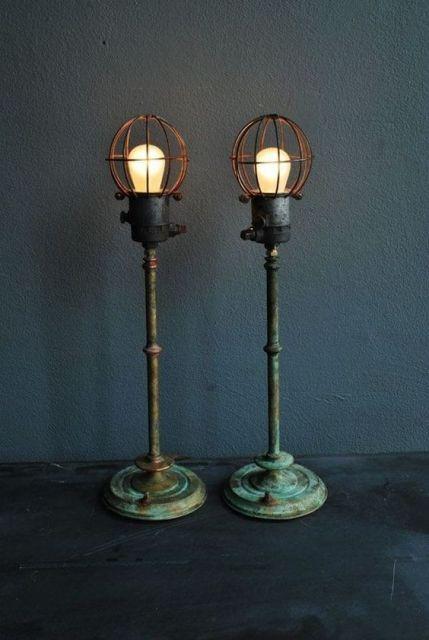Foto de duas luminárias de chão penduradas lado a lado. Elas são altas e tem base de metal com visual retrô. As lâmpadas são grandes e potentes, protegidas por estruturas de metal.