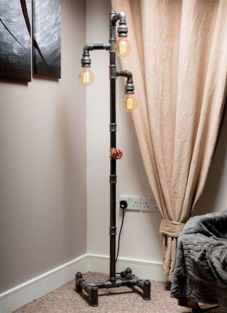 Foto de uma luminária feita a partir de canos. No topo, ela tem três extremidades, cada uma com uma lâmpada.