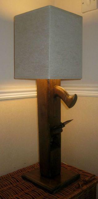 Foto de uma luminária com a lâmpada coberta por uma espécie de papel branco e a base feita a partir de madeira.