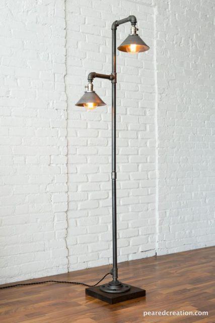 Foto de uma luminária de chão alta com um cano que termina em duas extremidades, cada uma com uma lâmpada protegida por estruturas metálicas que se parecem com chapéus.