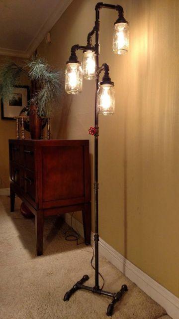 Foto de uma luminária de chão alta com saída para quatro lâmpadas no topo, cada uma delas protegida por vidros.