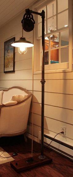 Foto de uma luminária de chão ligada na tomada. Ela é alta e tem uma roldana no topo que sustenta uma lâmpada.