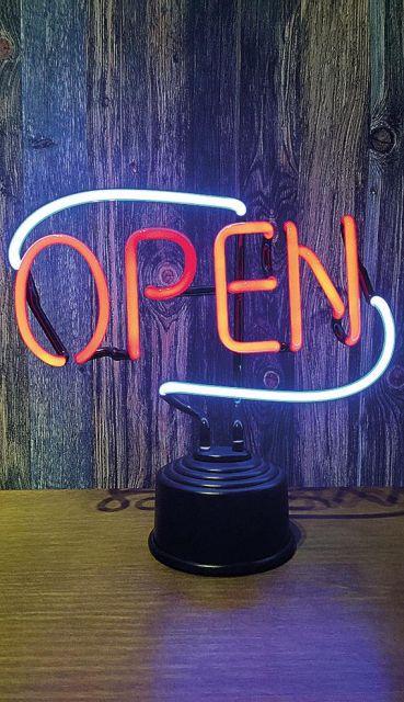 """Foto de uma luminária de mesa com letreiro em cores neon escrito """"Open""""."""