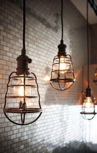 Foto de três luminárias retrô penduradas no teto por fios. As lâmpadas são envoltas por um material metálico que parece uma mini jaula.