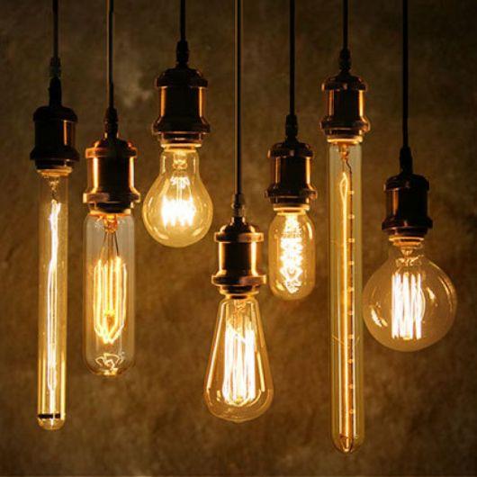 Foto de diversas lâmpadas penduradas no teto por fios com formatos de todos os tipos.
