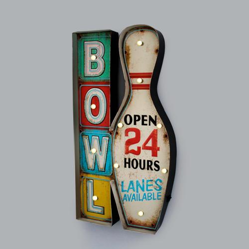 """Foto de uma luminária de parede com o desenho de um pino de boliche e quadrados com letras ao seu lado. Dentro do pino está escrito """"Open 24 Hours / Aberto 24 Horas"""" e ao lado """"Bowl / Boliche"""""""