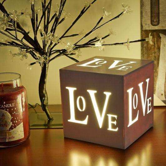 """Foto de um quadrado com interior iluminado e todas as extremidades com aberturas que formam a palavra """"Love""""."""