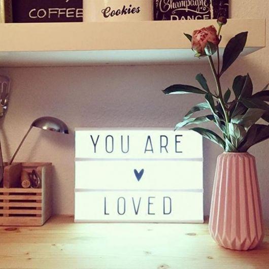 """Foto de uma luminária em formato quadrangular com os dizeres """"You Are Loved"""""""