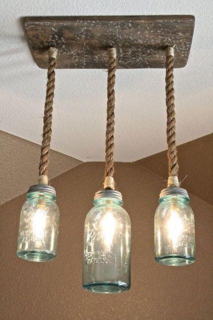 Foto de três lâmpadas ligadas a uma madeira pendurada no teto por uma corda. As lâmpadas são envoltas por recipientes de vidro que parecem potes.